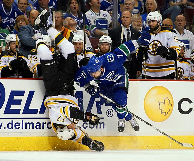 Vancouver Canucks defenseman Dan Hamhuis knocks Boston Bruins forward Milan Lucic off his skates with a hard check during Game 1 of the 2011 Stanley Cup Finals.