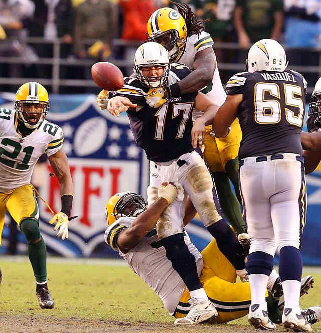 Chargers quarterback Philip Rivers manages to pass the ball, even with two Packers climbing all over him.