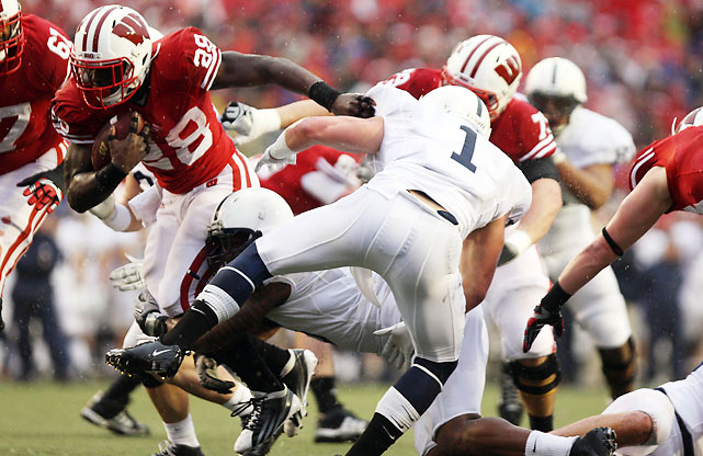 So much for Jay Paterno's plans to slap a yellow post-it note bearing his father's name on the Big Ten championship game trophy. Wisconsin secured the Leaders Division title thanks to another monster day from Montee Ball (pictured), who rushed for 156 yards and four touchdowns to bring his season total to a whopping 34.