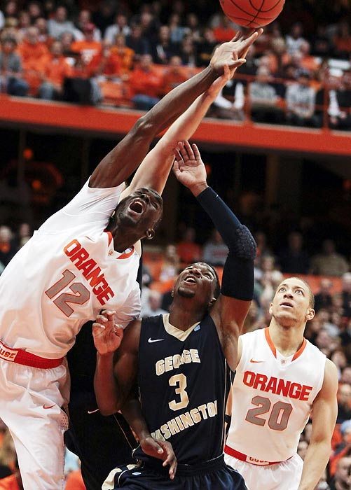 Syracuse center Baye Moussa Keita leaps over George Washington guard Tony Taylor to get a rebound during the Orange's easy 85-50 win.
