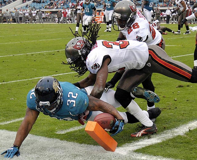 Jacksonville running back Maurice Jones-Drew dives under Tampa Bay's E.J. Biggers to score a touchdown. Jones-Drew had two scores in the Jaguars' 41-14 rout.