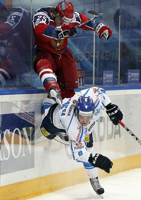 Russia's Igor Makarov (top) tries to hitch a ride on Finland's Mikko Kousa during their Channel One Cup hockey game in Moscow. Sweden won the cup; Russia finished third.