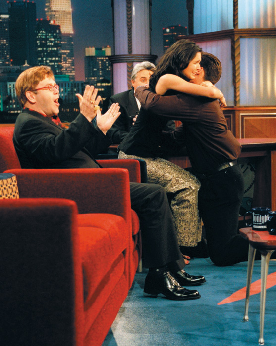 Former New York Giants cornerback Jason Sehorn proposes to actress Angie Harmon on a 1998 episiode of  The Tonight Show with Jay Leno . Elton John, who was also a guest on the show, looks on and claps.