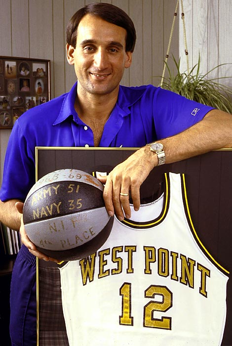 Krzyzewski poses with his retired #12 West Point jersey and a game ball from Army's 51-35 regular season victory over Navy during the 1968-69 season. Krzyzewski was the head coach at Army from 1975 to 1980.