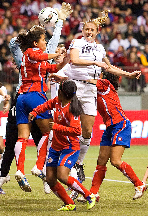 Rachel Buehler leaps for a header among a throng of Costa Rica players.