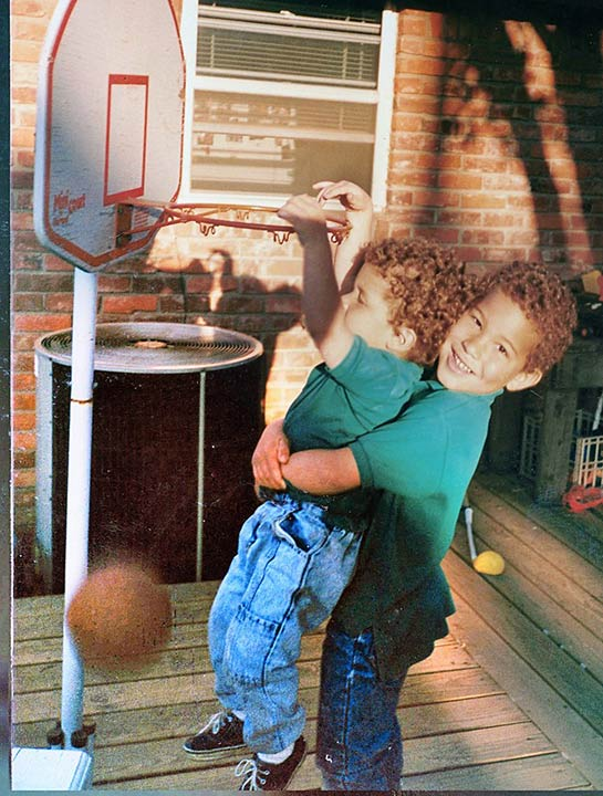 A 2-year-old Blake gets a boost from older brother Taylor (5) to reach a hoop at their home in Oklahoma. Clearly he wouldn't need help for long.