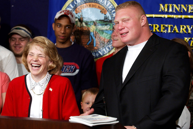 "Brock Lesnar makes former Minnesota Secretary of State Mary Kiffmeyer laugh at an August 2003 press conference. Lesnar told reporters that he was on the cover of the Minnesota legislative manual for students because the then 56-year-old ""Secretary of State likes big men."" What a jokester."