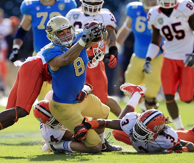 UCLA tight end Joseph Fauria lunges forward as Illinois defenders Patrick Nixon-Youman (4) and Tavon Wilson (3) make the tackle during the Fight Hunger Bowl in San Francisco.