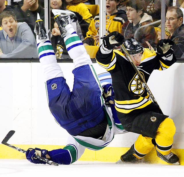 Bruins winger Brad Marchand trips Vancouver's Sami Salo in the second period of the Canucks' 4-3 win in Boston on Saturday night. Marchand was called for a tripping penalty and ejected from the rematch of last year's Stanley Cup Finals for the hit.