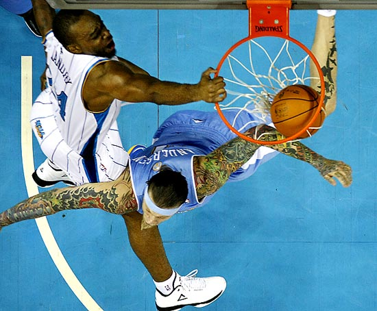 "New Orleans power forward Carl Landry dunks over Denver center Chris ""Birdman"" Anderson in the first half of the Nuggets' 96-88 win at the Hornets."