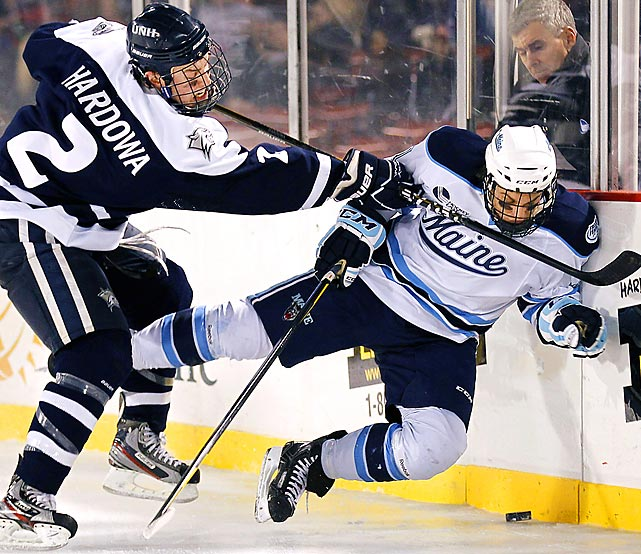 New Hampshire's Connor Hardowa checks Maine's Theo Andersson during the third period of Maine's 5-4 overtime win at Fenway Park on Sunday.