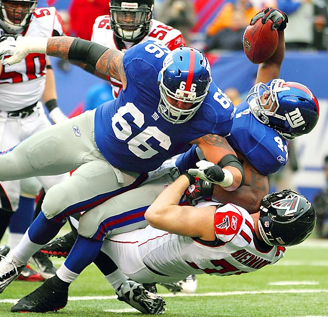 New York Giants running back Ahmad Bradshaw (44) gets some help from offensive tackle David Diehl (66) as he is tackled by Falcons defensive end Kroy Biermann during their NFC Wild-Card game at MetLife Stadium. Bradshaw had 64 yards on the ground in the Giants' 24-2 win.