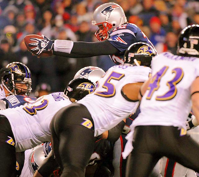 Patriots quarterback Tom Brady dives over the pile for a touchdown during New England's victory over Baltimore.