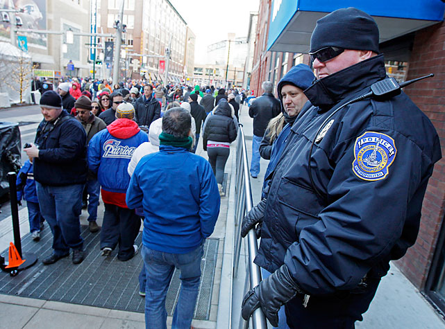 Officer David Bryant of the Indianapolis Metropolitan Police watches the crowd at the Super Bowl Village.