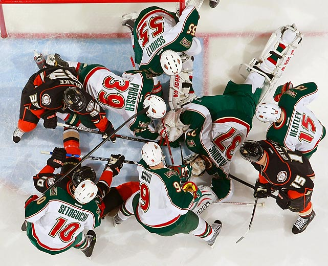 Minnesota Wild goalie Josh Harding (37) attempts to cover the puck while his teammates battle with several Anaheim players for position in front of the net.