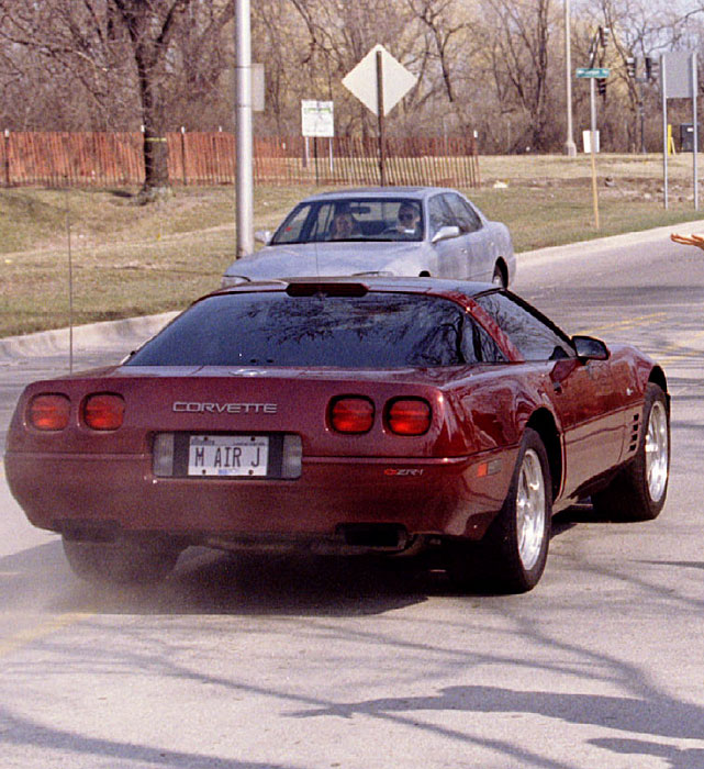 "Michael Jordan speeds past fans outside the Bulls practice facility after announcing his first comeback. His vanity plate: ""M AIR J."""