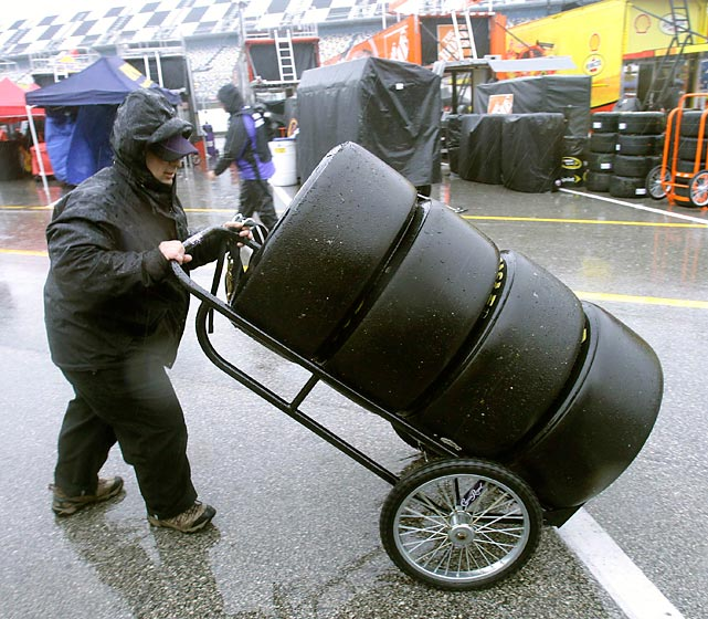 A NASCAR crew worker pushes a set of tires through the garages during a rain delay at the 2010 NextEra Energy Resources 250, the NASCAR Camping World Truck Series race held at Daytona International Speedway two days before the Daytona 500. The intense rain on the scheduled day of the 2010 race forced its postponement until the next day. Timothy Peters eventually claimed the victory.