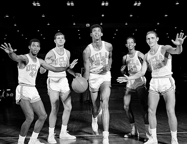 Lew Alcindor dribbles a ball while teammates (L-R) Mike Warren, Mike Lynn, Edgar Lacey and Don Saffer pose next to him. Abdul-Jabbar won three titles while at UCLA.
