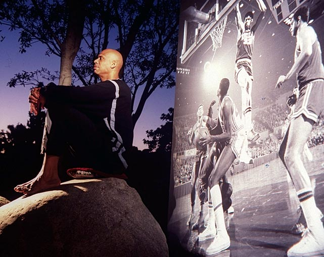 Kareem Abdul-Jabbar poses with video of himself during his UCLA days playing behind him. Along with being UCLA's career leader in points per game, Abdul-Jabbar is second all-time in total rebounds and rebounds per game.