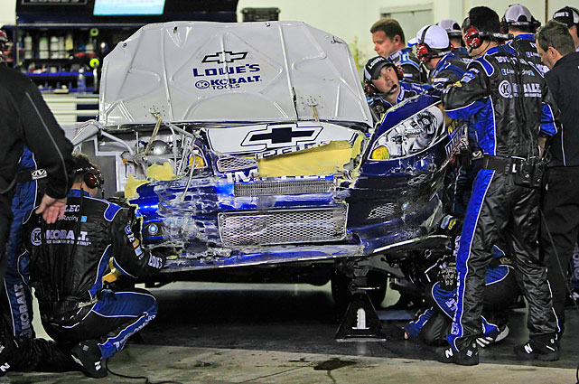 Crew members work on Johnson's car, but it wouldn't get back on the track Monday.