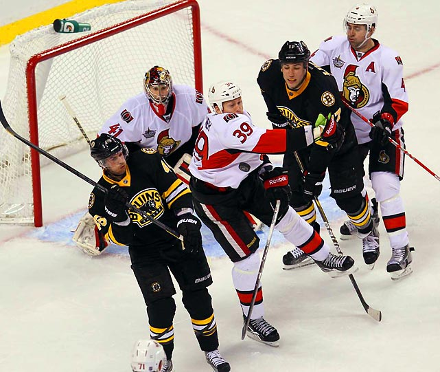 Senators' defenseman Matt Carkner battles with a pair of Bruins in front of Ottawa's net.