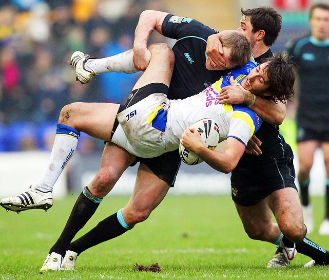 Warrington's Stefan Ratchford gets tackled by London's Craig Gower in an English rugby match.
