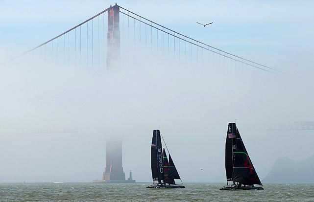 A pair of ships from defending America's Cup champion Oracle Racing sails near the South Tower of the Golden Gate Bridge in San Francisco Bay. San Francisco will host the America's Cup in 2013.