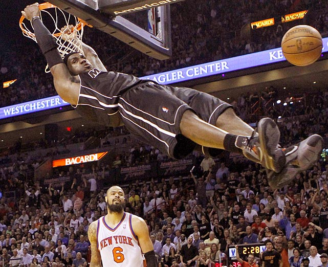 LeBron James hangs on the rim after dunking during the Heat's win over the Knicks.