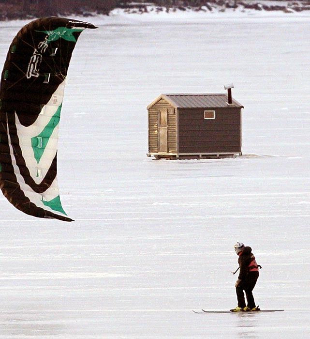 A kite skier sails past an ice fishing shack on Long Lake in Naples, Maine.
