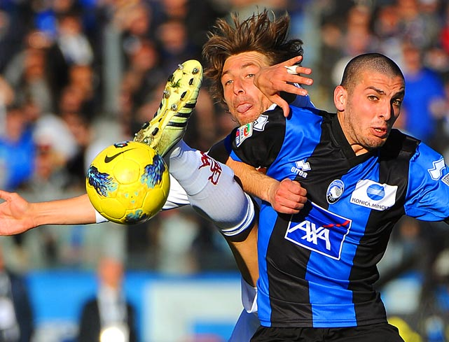Atalanta midfielder Alessandro Carrozza (right) fights for the ball with Roma defender Gabriel Heinze during an Italian Serie A match.