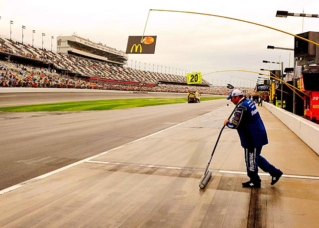 A pit worker does his part to dry the track at Daytona International Speedway on Sunday. The start Daytona 500 was pushed back from Sunday afternoon to Monday evening.