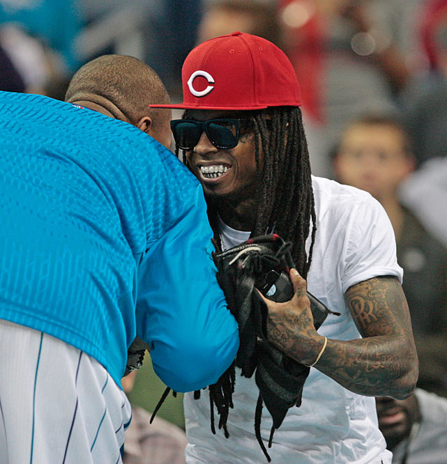 Lil Wayne greets Hornets forward David West before the start of a 2010 Hornets-Heat game in New Orleans.