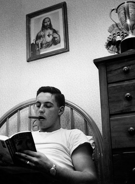 Jean Béliveau lies in bed reading Tolstoy's Anna Karenina  with a cigar in his mouth in Dec. 1952.