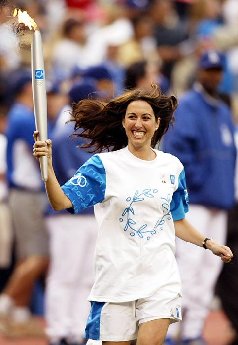 Evans carries the Olympic torch in 2004. She won the 400- and 800-meter freestyle at the U.S. National Championships 12 times each, the most national titles in one event by any American swimmer.