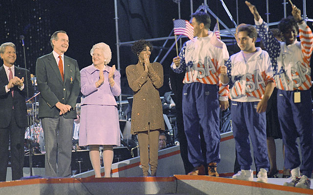 "Houston helped welcome the Olympic flag to the Georgia Dome after the 1992 Barcelona Olympics ended. Georgia Olympians (right) joined Houston, along with President George H. W. Bush (left), James Brown, Dick Clark and Carlos Santana. Houston recorded ""One Moment in Time"" for NBC's coverage of the 1988 Seoul Games."