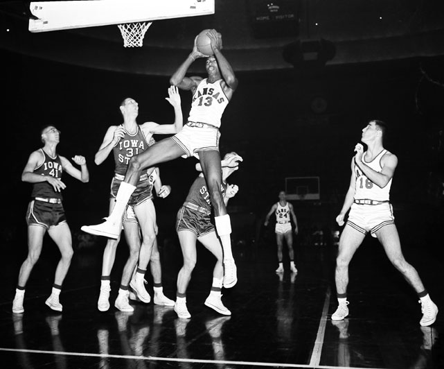 Wilt Chamberlain grabs a rebound during a 1956 game against Iowa State. During his college career he averaged over 30 points per game and was twice selected to All-American teams.