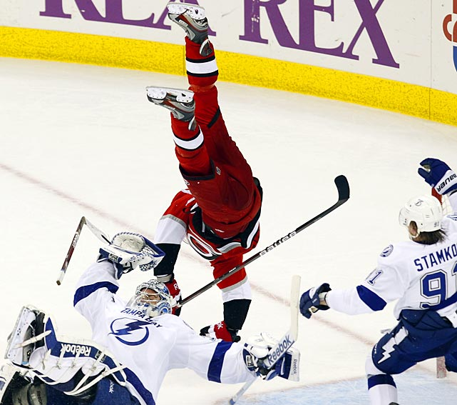 The Carolina Hurricanes' Brandon Sutter flies over Tampa Bay goalie Mathieu Garon as Lightning forward Steven Stamkos looks on.