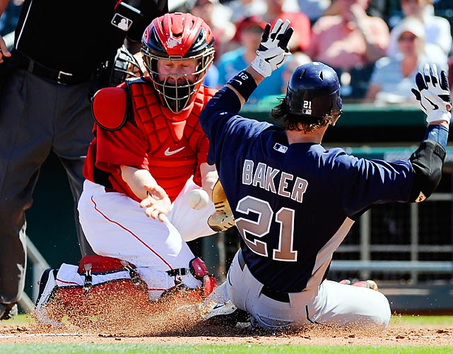 John Baker of the Padres scores on a double by Ryner Liriano, beating the throw to Reds catcher Ryan Hanigan.