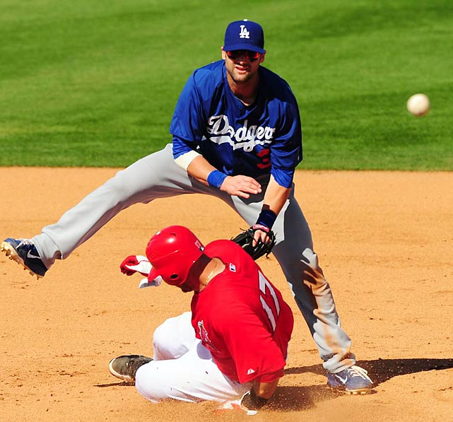 The Angels' Chris Iannetta slides underneath the Dodgers' Adam Kennedy during a spring training game in Arizona.