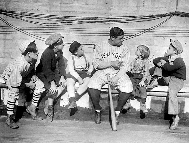 Ruth, the most popular athlete of his era, poses with a group of children.