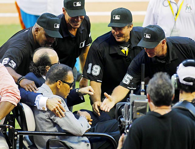 The umpiring crew greets Muhammad Ali, who took part in the ceremonial first pitch at Marlins Park on Wednesday night.