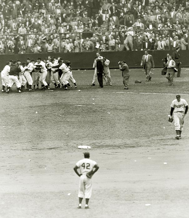 "Brooklyn's Jackie Robinson looks on as the New York Giants mob Bobby Thomson at home plate after Thomson won the pennant with his ""Shot Heard 'Round the World."""