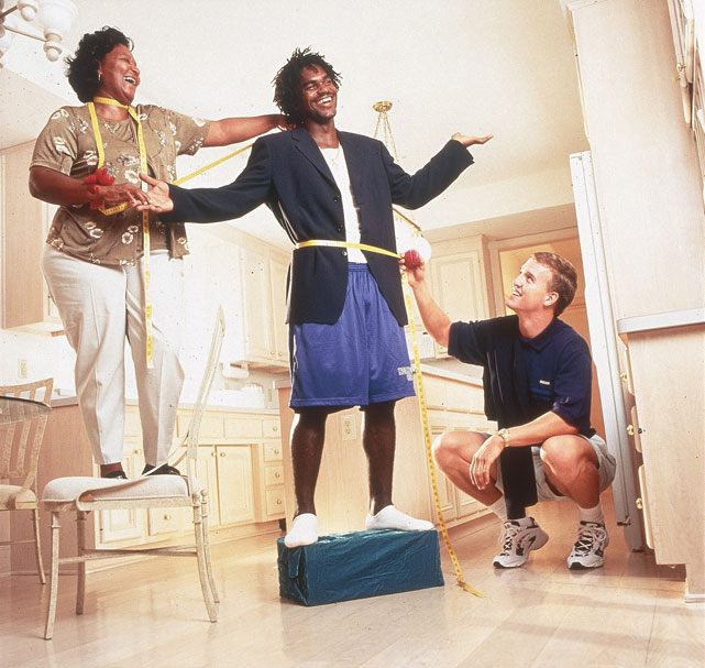 Manning helps Edgerrin James' mother Julie fit the running back for a suit in 1999.