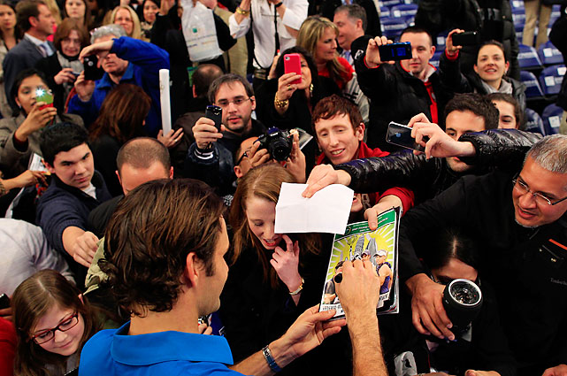 Federer appeases the autograph and camera-phone-picture seekers.