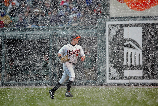 With a heavy snow falling, Orioles rightfielder Jay Gibbons searches in vain for a fly ball hit by Indians DH Ellis Burks during the season opener in Baltimore. The ball fell in for an RBI single and play was subsequently stopped for around 15 minutes to let the snow shower pass.