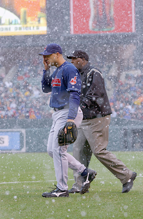 Cleveland's Travis Hafner walks back to the field with firstbase umpire Chuck Meriwether before a 13 miniute snow delay was called on opening day. The Orioles would go onto win 6-5.