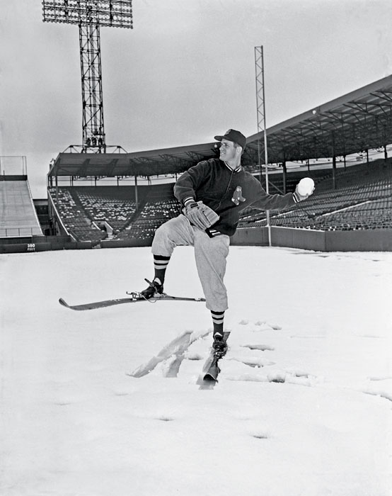 Mel Parnell, ace left-hander for the Red Sox, pitches huge snowball as he wears skis on the pitchers mound at Fenway Park. Parnell was slated to open the season against Washington, but freak snowstorm forced postponement of the game.