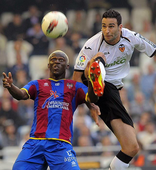 Valencia's French defender Adil Rami leaps over Levante's forward Arouna Kone to fight for the ball during a Spanish league soccer match.
