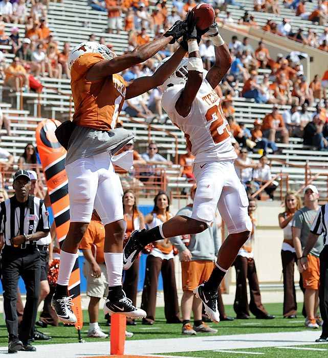 Texas defensive back Josh Turner intercepts a pass in front of wide receiver Mike Davis during the Longhorns spring football game.