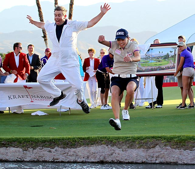 Sun Young Yoo of Korea and caddie Adam Woodward take the traditional jump into Poppy's Pond by the 18th green after Yoo won in a playoff during the final round of the Kraft Nabisco Championship.